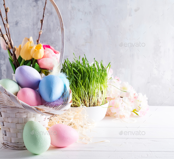 Easter basket filled with colorful hand painted Easter Eggs over a light background - Stock Photo - Images