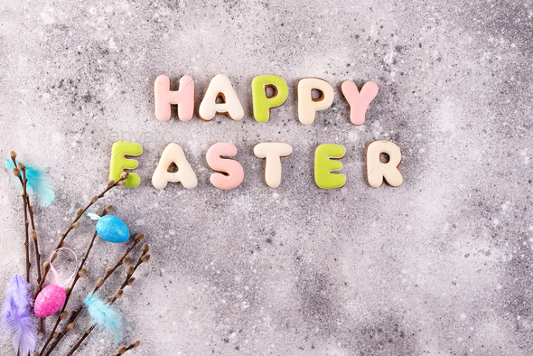 Easter eggs and homemade glazed cookies on a stone background, flat lay - Stock Photo - Images