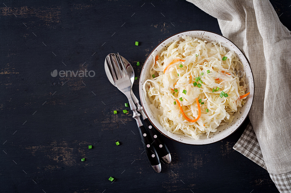 Fermented cabbage. Vegan food. Sauerkraut with carrot and spices in bowl on the dark background.  - Stock Photo - Images