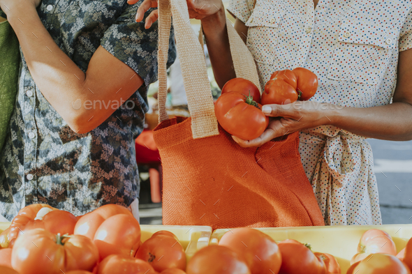 Friends buying fresh tomatoes at a farmers market - Stock Photo - Images