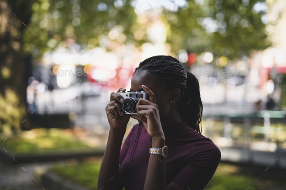 Woman taking photos with a vintage film camera - Stock Photo - Images