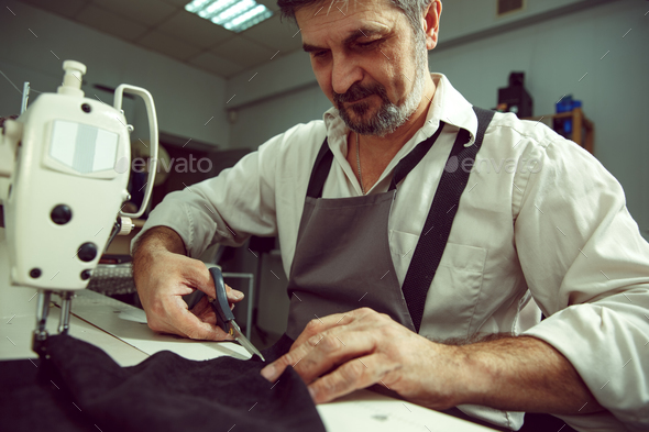 Sewing process of the leather belt. Old Man's hands behind sewing. - Stock Photo - Images