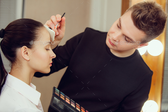 Professional makeup artist working with beautiful young woman - Stock Photo - Images