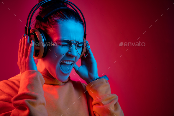 Fashion pretty woman with headphones listening to music over neon background - Stock Photo - Images