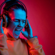 Fashion pretty woman with headphones listening to music over neon background - PhotoDune Item for Sale