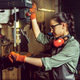Busy and serious craftswoman grinding timbers with special machine. - PhotoDune Item for Sale