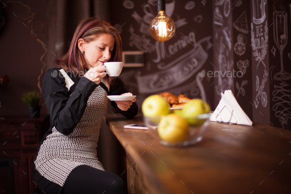 Adult woman enjoys her cup of coffe at bar counter