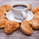 Freshly baked croissants on rustic wooden table with cup of coffee - PhotoDune Item for Sale