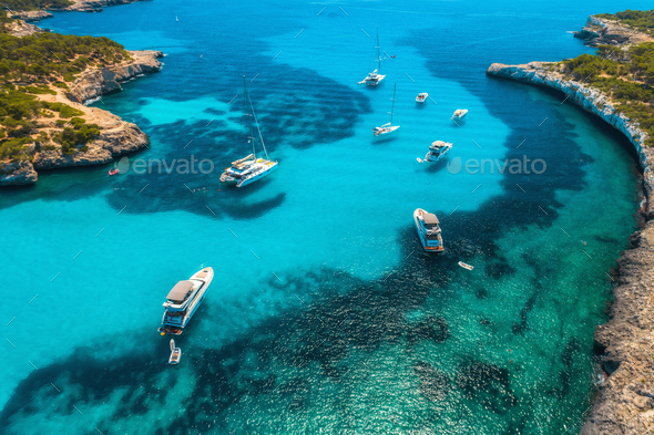 Boats and luxury yachts in transparent sea at sunny day. Aerial - Stock Photo - Images
