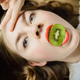 caucasian girl holds kiwi in mouth - PhotoDune Item for Sale