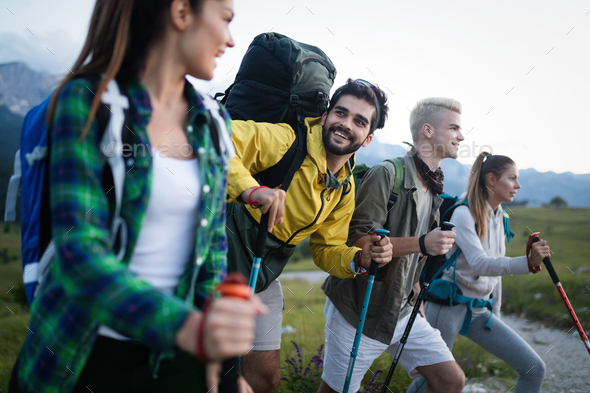 Four happy friends are looking on mountains and having fun together - Stock Photo - Images