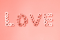 The word LOVE made from gerbera flowers on a background in a color of the year 2019 Living Coral - PhotoDune Item for Sale