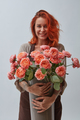 Young woman with a big vase of roses flowers in a color of the year 2019 Living Coral Pantone on a - PhotoDune Item for Sale