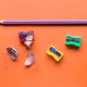 colored pencils and pencil sharpener on orange board - PhotoDune Item for Sale