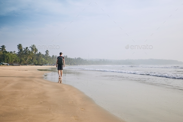 Lonely man on the beach - Stock Photo - Images