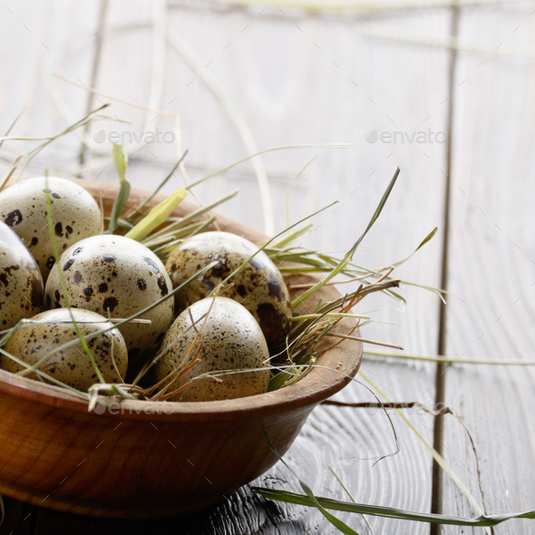 Fresh organic quail eggs in wooden bowl on rustic kitchen table. - Stock Photo - Images