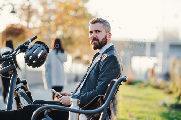 Businessman commuter with bicycle and smartphone sitting on bench in city. - Stock Photo - Images