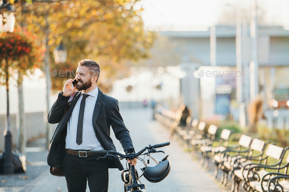 Businessman commuter with bicycle walking home from work in city, using smartphone. - Stock Photo - Images