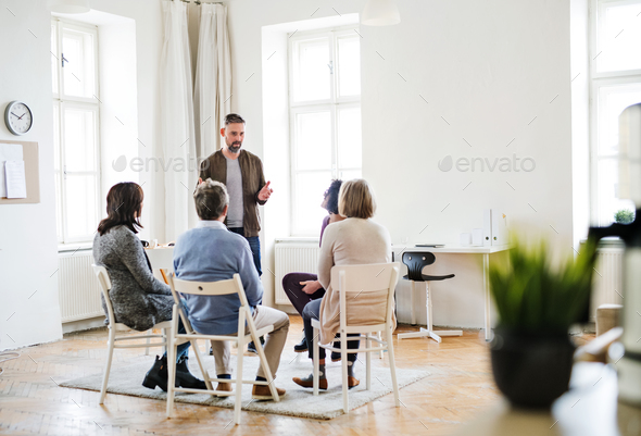 A man talking to other people during group therapy. - Stock Photo - Images