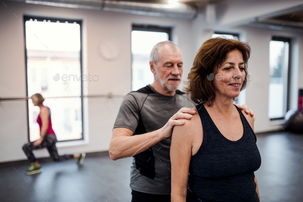 A senior woman in gym doing exercise with a personal trainer. - Stock Photo - Images