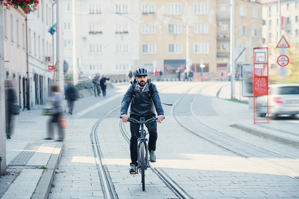 Hipster businessman commuter with electric bicycle traveling home from work in city. - Stock Photo - Images