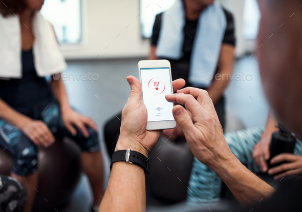 A midsection of group of seniors with smartphone in gym checking heart rate. - Stock Photo - Images