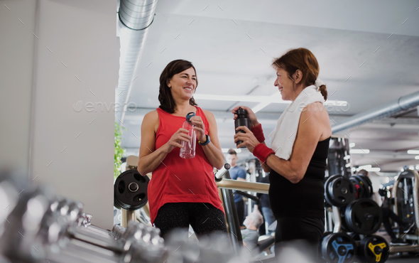 Two senior women in gym resting after doing exercise, holding water bottles. - Stock Photo - Images