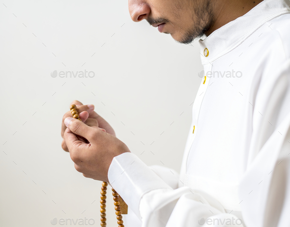Muslim man using misbaha to keep track of counting in tasbih - Stock Photo - Images