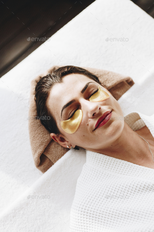 Woman relaxing with a golden eye mask treatment - Stock Photo - Images