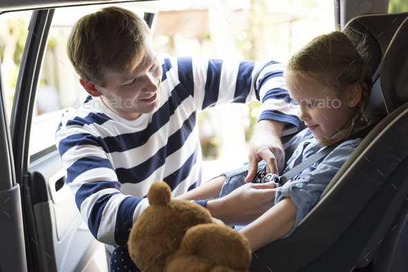 Father helping to put on the seat belt - Stock Photo - Images