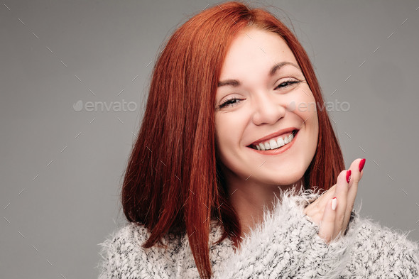 Charming woman with ginger hair smiling and putting hands together - Stock Photo - Images