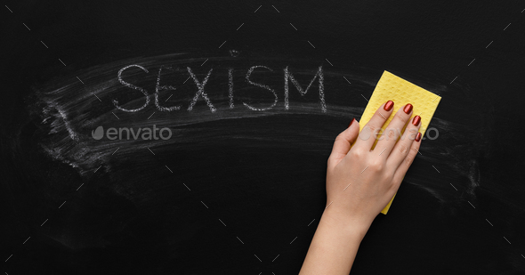 Sexism written on chalkboard and hand with sponge - Stock Photo - Images