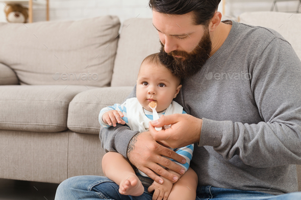 Father feeding his cute baby son at home - Stock Photo - Images