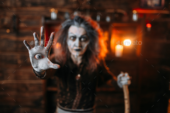 Scary witch with an eye in the palm, seance - Stock Photo - Images