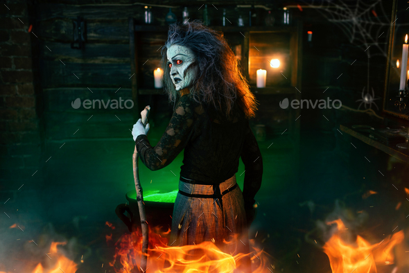 Scary witch cooking green brew and reads the spell - Stock Photo - Images