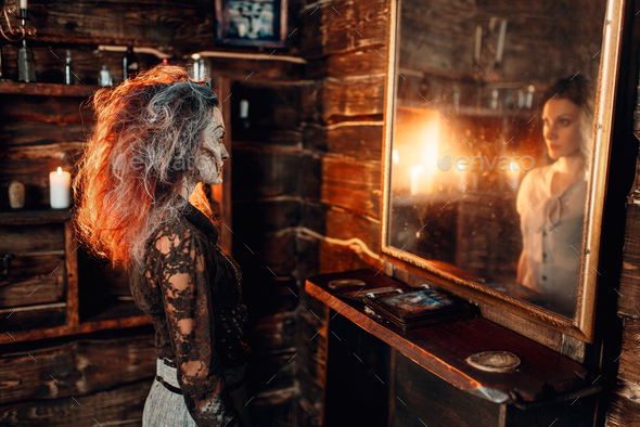 Witch at the mirror, young woman in the reflection - Stock Photo - Images