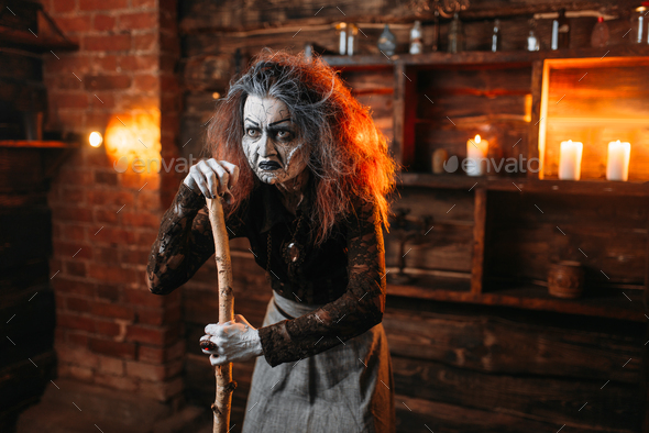 Scary witch stands leaning on a cane, seance - Stock Photo - Images