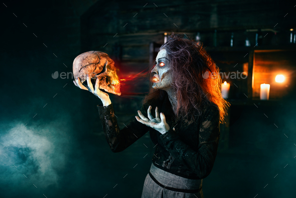 Scary witch holds human skull and reads the spell - Stock Photo - Images