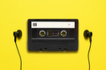 Headphones and old audio cassette on yellow background - PhotoDune Item for Sale