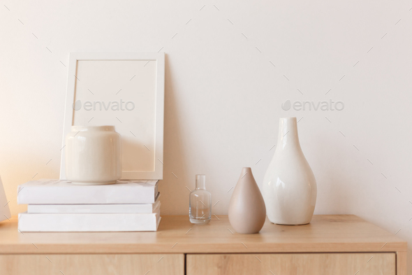 Neutral colored vases, photo frame and stack of books on bureau shelf - Stock Photo - Images