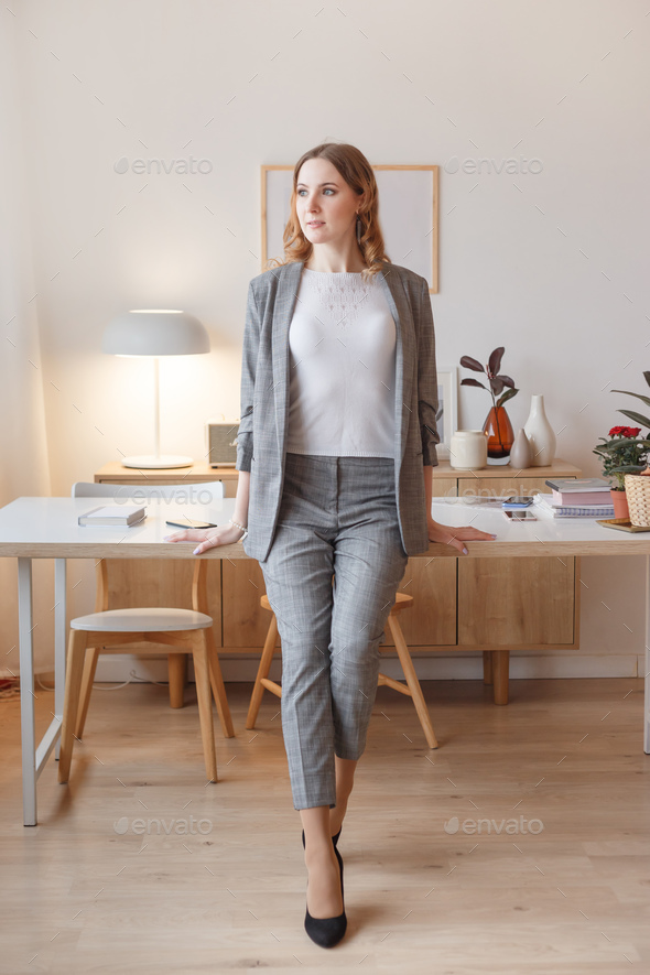 Young boss woman in a gray stylish suit stands in her own creative office - Stock Photo - Images