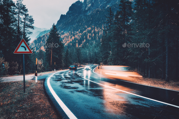 Blurred cars in motion on the road in autumn forest in rain