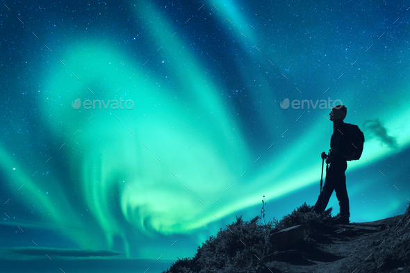 Aurora borealis and silhouette of a woman with backpack at night - Stock Photo - Images