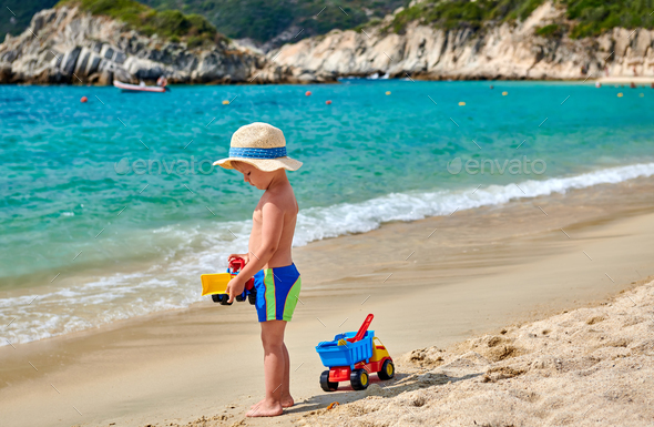 Toddler boy on beach with toys - Stock Photo - Images