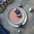 Glazed ceramic plate in a color of Living Coral Pantone with painted violet Easter eggs on a gray - PhotoDune Item for Sale