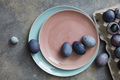 Blue and violet Easter eggs on a ceramic plate in a color of Living Coral Pantone on a gray stone - PhotoDune Item for Sale