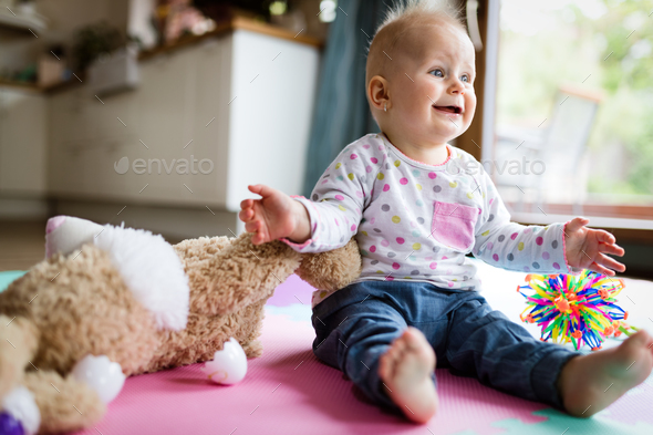 Happy one year old girl sitting with plush toy - Stock Photo - Images