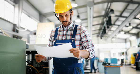 Portrait of an architect builder studying layout plans of plant - Stock Photo - Images
