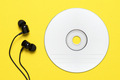 Compact disc and earbuds on yellow background - PhotoDune Item for Sale