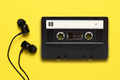 Earphones and audio cassette on yellow background - PhotoDune Item for Sale